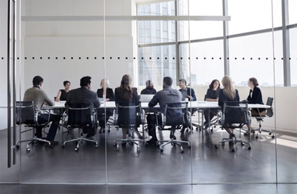 About Us | Group of businessmen and women having a meeting